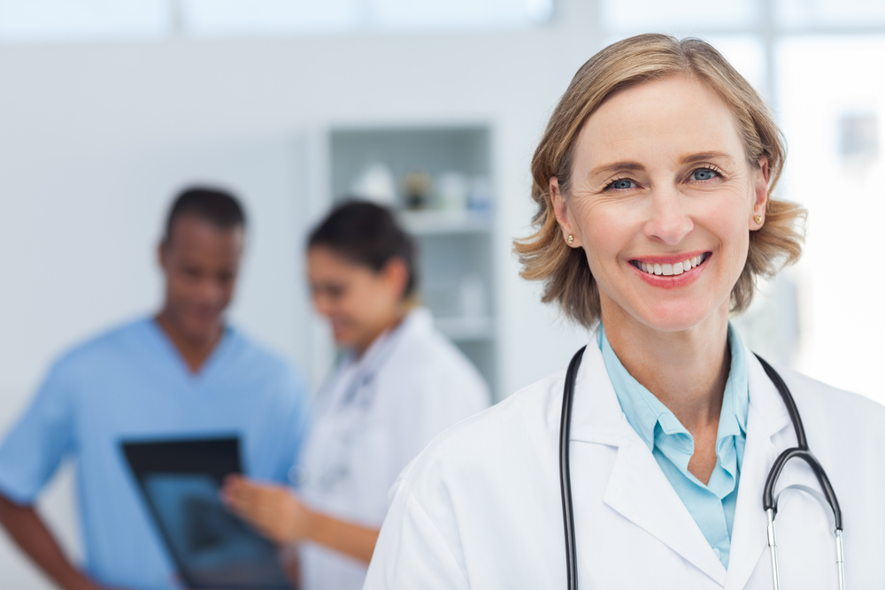 Woman doctor smiling and looking to the camera while a medical team is working
